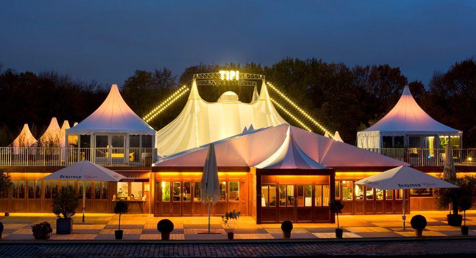 Das Tipi am Kanzleramt mit Terrassen und Lounges bei Nacht.